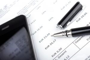 Smartphone und Stift auf Rechnung