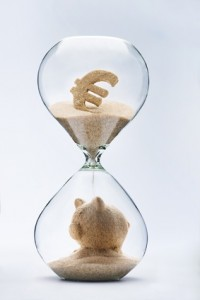 Banking concept. Piggy bank made out of falling sand from euro sign flowing through hourglass